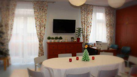 na zdjęciu sala terapii zajęciowej na pierwszym planie stół z białym obrusem mała choinką oraz czerwonymi lampionami w tle drewniana komoda na której stoją rośliny doniczkowe nad komodą telewizor zawieszony na ścianie