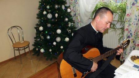na zdjęciu osoba księdza grającego na gitarze z choinką w tle