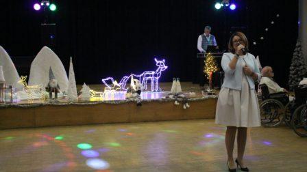 na zdjęciu kobieta dyrektor domu przemawia do zgromadzonych