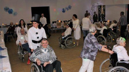 na zdjęciu sala z tańczącymi w kole osobami na wózkach inwalidzkich które pchają pracownicy