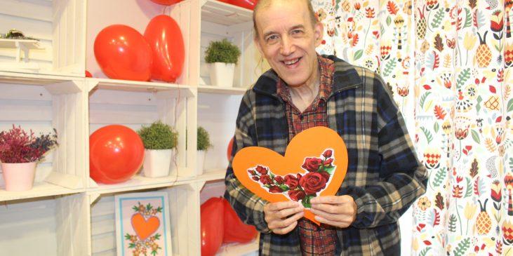 na zdjęciu uśmiechnięty mężczyzna trzyma w rękach papierową laurkę w kształcie serca