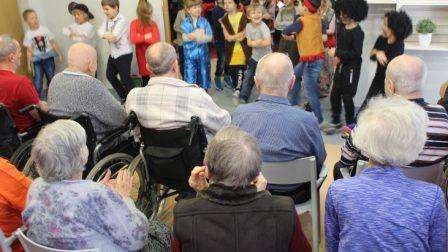na zdjęciu mieszkańcy oglądający występ przedszkolaków