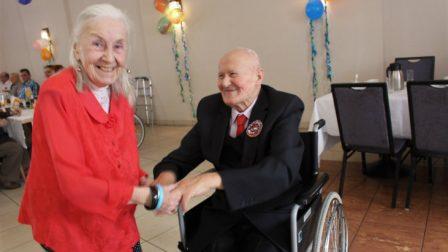 na zdjęciu uśmiechnięta kobieta tańczy z uśmiechniętym mężczyzną