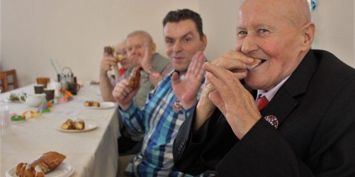na zdjęciu uśmiechnięci ludzie jedzą pączki i machają do obiektywu