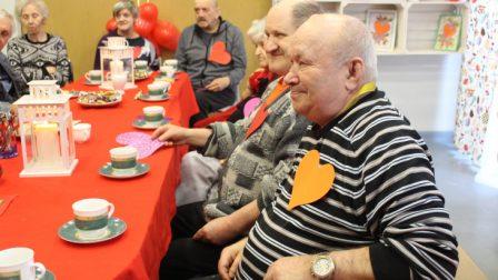 na zdjęciu mieszkańcy siedzą przy odświętnie udekorowanym stole i piją kawę