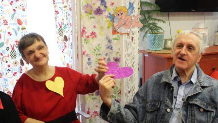 na zdjęciu mężczyzna i kobieta pozują trzymając w rękach brokatową walentynkę w kolorze fioletowym