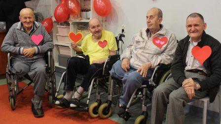 na zdjęciu czterech mężczyzn pozuje z przymocowanymi do ubrania kotylionami w kształcie serca