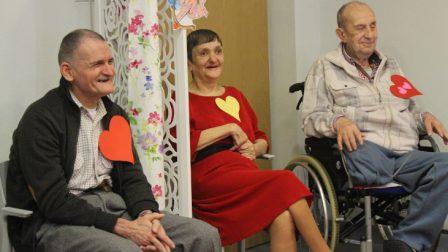 na zdjęciu mężczyzna siedzi na krześle obok parawanu za parawanem na krześle siedzi kobieta