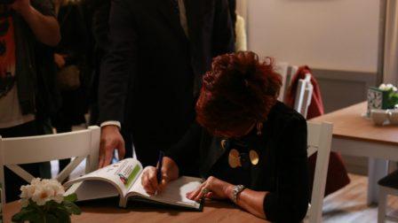 na zdjęciu Jolanta Kwaśniewska wpisuje się do Księgi Pamiątkowej