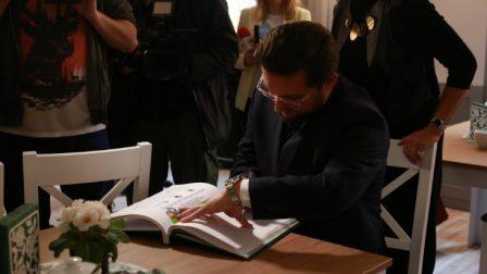 na zdjęciu prezydent Katowic wpisuje się do Księgi Pamiątkowej