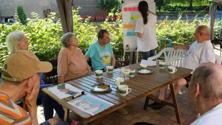 na zdjęciu znajduje się grupa mieszkańców siedząca w ogrodzie