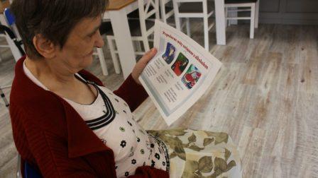 na zdjęciu znajduje się mieszkanka czytająca broszurę informacyjną