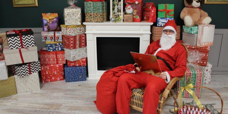 Na zdjęciu znajduje się Mikołaj na tle prezentów.